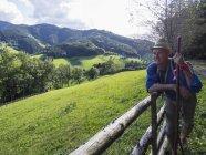 Старший чоловік, спираючись на дерев'яний паркан у середній Шварцвальдом, Баден-Вюртемберг, Німеччина — стокове фото