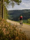 Man riding bicycle on cycling tour on road in Northern Black Forest, Germany — Stock Photo