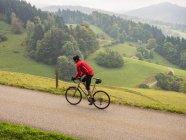 Человек на велосипеде в деревне Южный Шварцвальд, Баден-Вюртемберг, Германия — стоковое фото