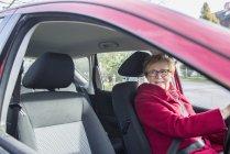 Mulher sênior feliz sentado no carro e olhando pela janela — Fotografia de Stock