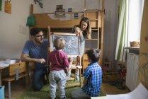 Kleinkind jungen schreiben an Tafel mit Eltern und Bruder ansehen — Stockfoto