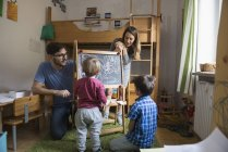 Toddler boy writing on blackboard with parents and brother watching — Stock Photo