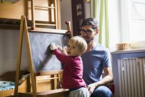 Toddler boy cleaning  blackboard while father watching — Stock Photo
