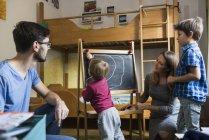 Bambino che scrive sulla lavagna con genitori e fratello guardando — Foto stock