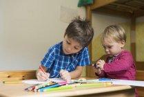 Frères dessin avec crayons de couleur à table — Photo de stock