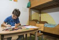 Niño para colorear con lápices de colores en la mesa - foto de stock