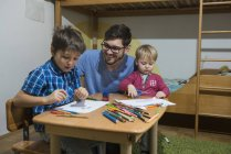 Brothers enjoying drawing with colored pencils while father smiling — Stock Photo