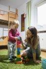 Mère jouant avec tout-petit fils avec des blocs de construction — Photo de stock