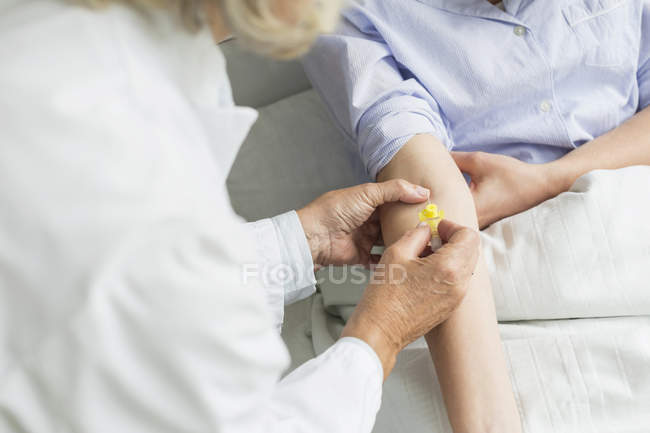 Doctor preparing infusion needle — Stock Photo