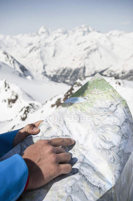 Man reading map in Alps mountains — young adult, travel destination ...