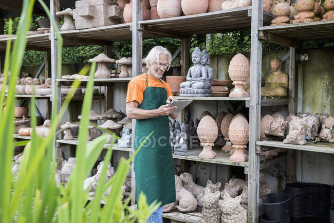 Male gardener checking inventory with tablet — Stock Photo
