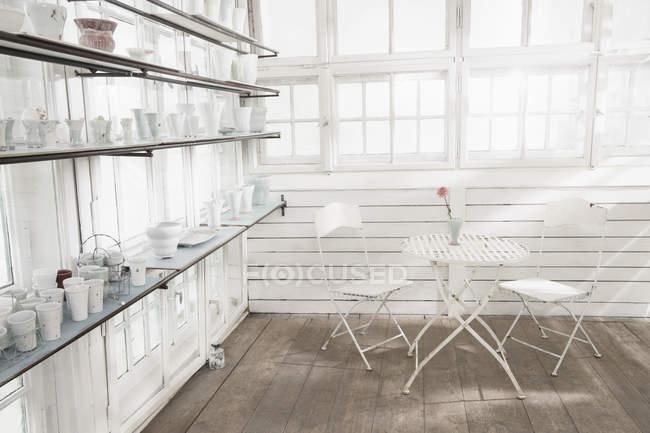 Фарфоровые вазы на полке в стеклянном доме — стоковое фото