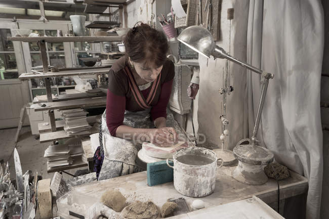 Female potter moulding clay in workshop — Stock Photo