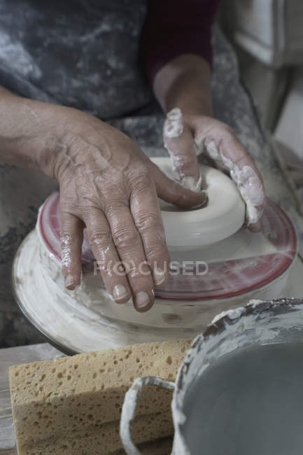 Potier femelle moulant l'argile en atelier — Photo de stock