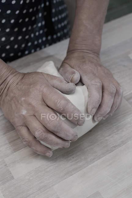 Potier pétrissage argile sur établi — Photo de stock