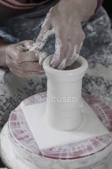 Argila de moldagem de oleiro usando esponja de limpeza — Fotografia de Stock