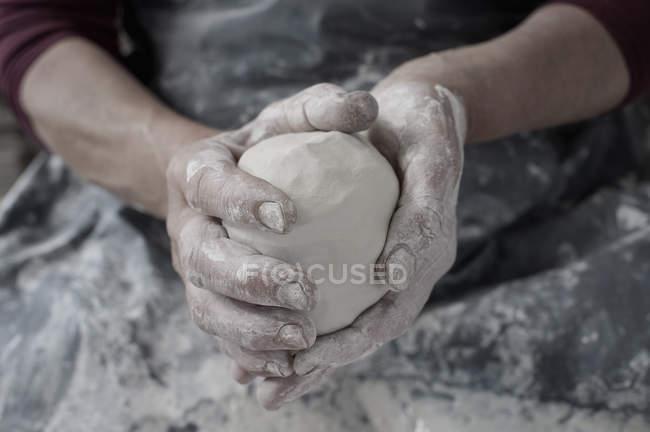 Mano del vasaio femminile che tiene argilla — Foto stock