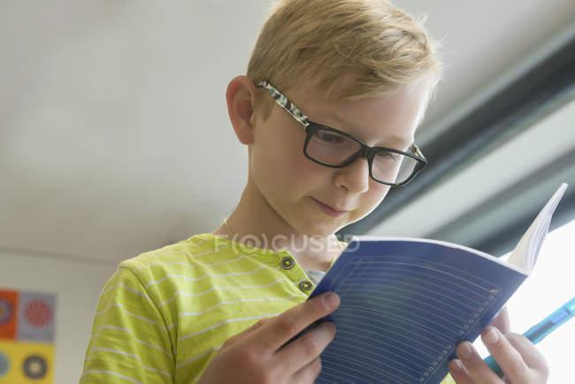 Écolier lisant un livre en classe — Photo de stock