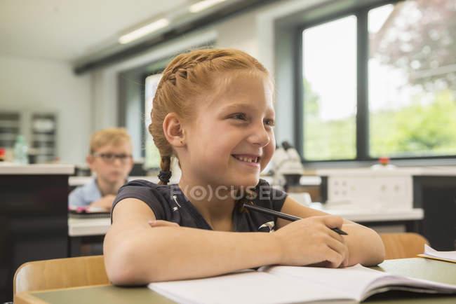 Écolière souriante en classe de biologie — Photo de stock