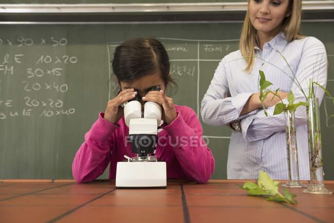Schoolgirl with teacher looking through a microscope — Stock Photo