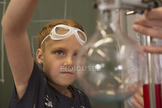 School girl with teacher doing experiments — Stock Photo