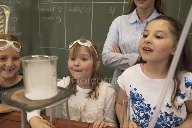 Teacher and schoolgirls conducting scientific experiments — Stock Photo