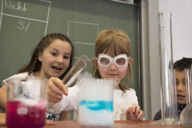 Schoolstudents mixing liquid in chemistry class — Stock Photo