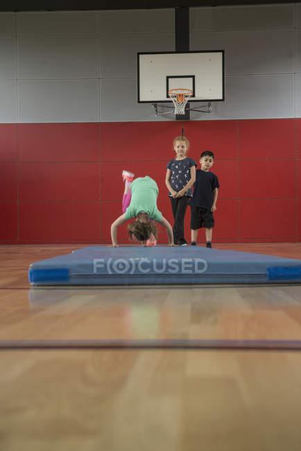 Mädchen tun Purzelbaum auf Gymnastikmatte — Stockfoto