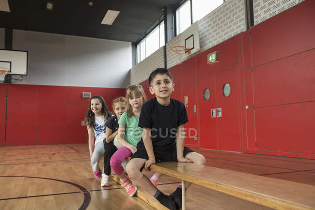 Children resting on bench in large gym — Stock Photo