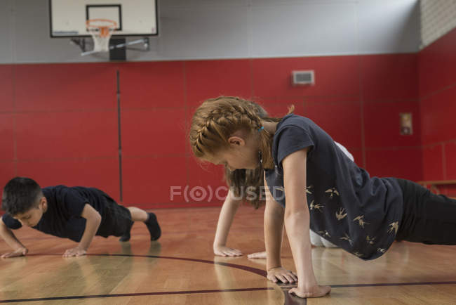 Children doing press-ups in sports hall — Stock Photo
