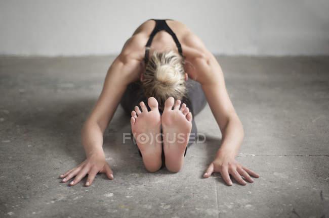 Женщина практикует uttanasana позу — стоковое фото