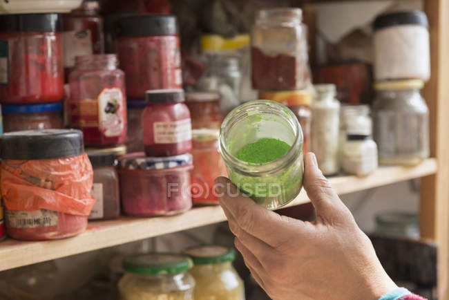 Artist's hand with colors and pigments — Stock Photo