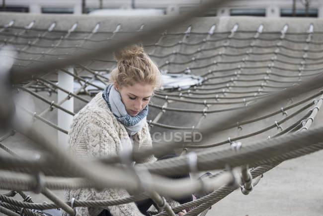 Жінка сидить на сходження мережі в дитячий майданчик — стокове фото
