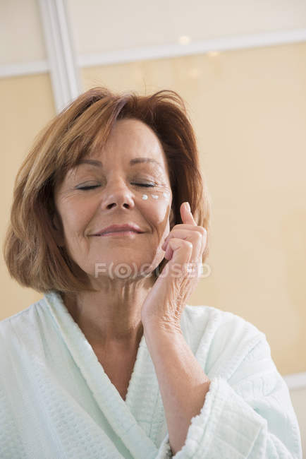 Senior woman applying moisturizer on face — Stock Photo
