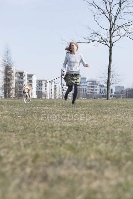 Mädchen im Park mit Hund laufen — Stockfoto
