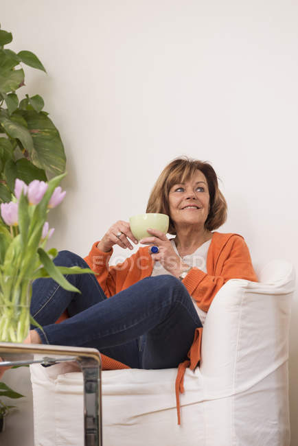 Woman dreaming while drinking tea at home — Stock Photo