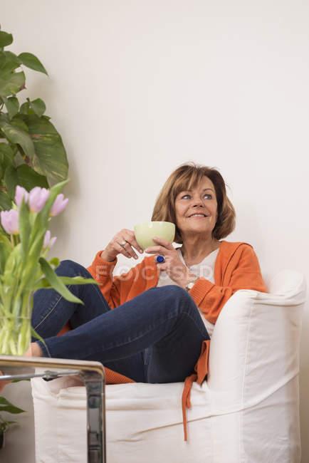 Жінка мріє попиваючи чай в домашніх умовах — стокове фото