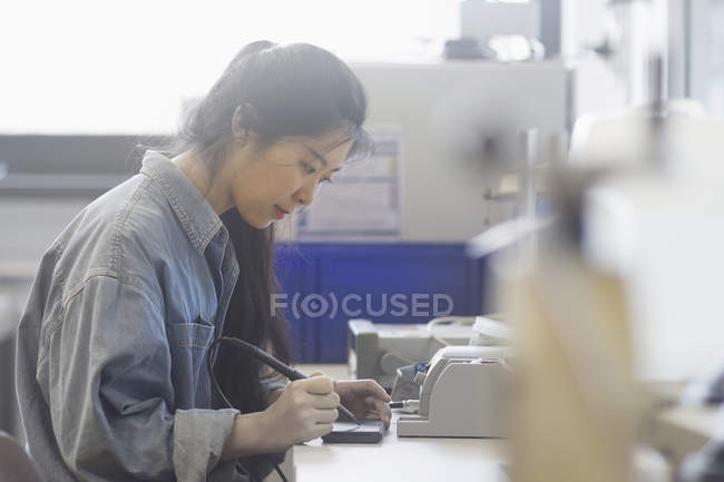 Female technician soldering electronic components — Stock Photo