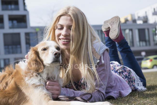 Mädchen im Park mit ihrem Hund liegend — Stockfoto