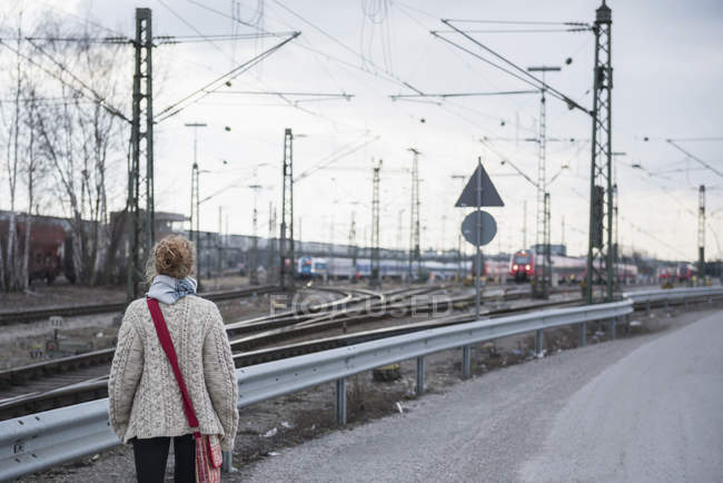 Woman curiously looking at train — Stock Photo