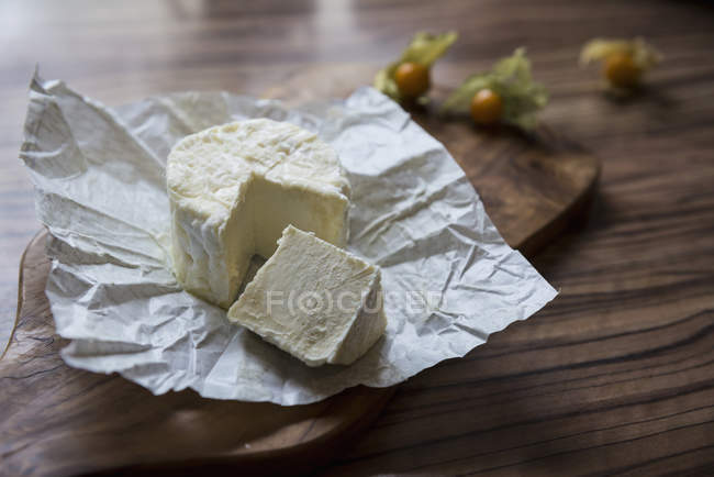 White cheese with slice on chopping board — Stock Photo