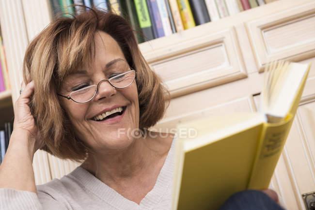 Senior woman reading in front of bookshelf — Stock Photo