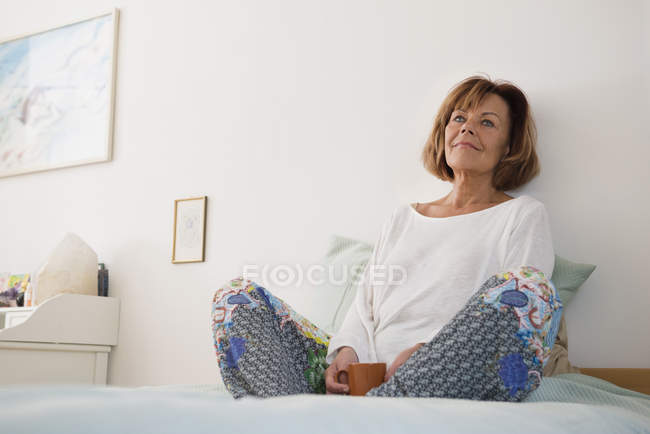 Senior woman sitting on bed — Stock Photo