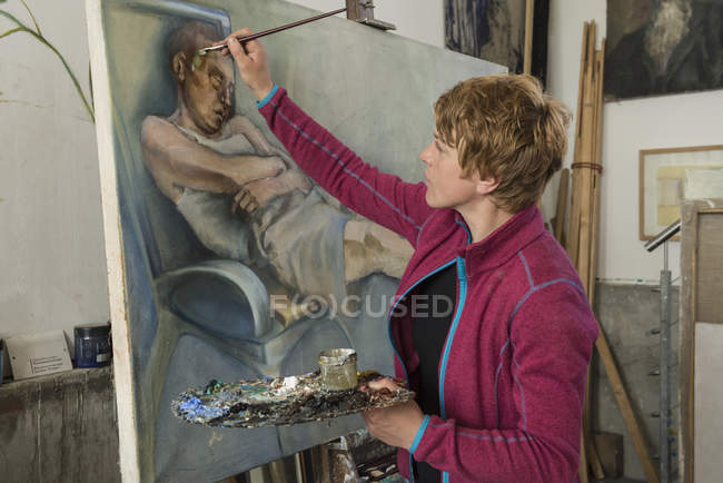 Woman painting at easel — Stock Photo