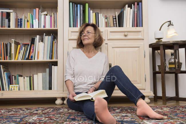 Frau sitzt am Bücherregal und liest — Stockfoto