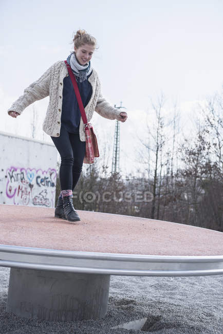 Young woman balancing on playground spinner, — Stock Photo