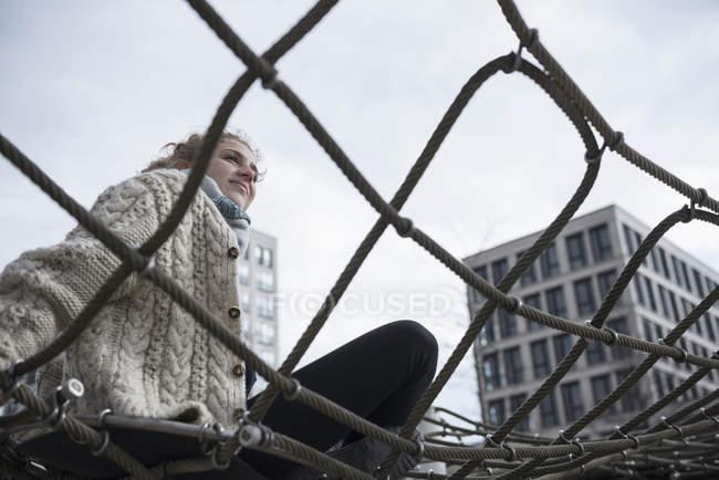 Женщина сидит на сетке для лазания — стоковое фото