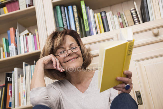 Senior woman reading in front of bookshelf — Stock Photo