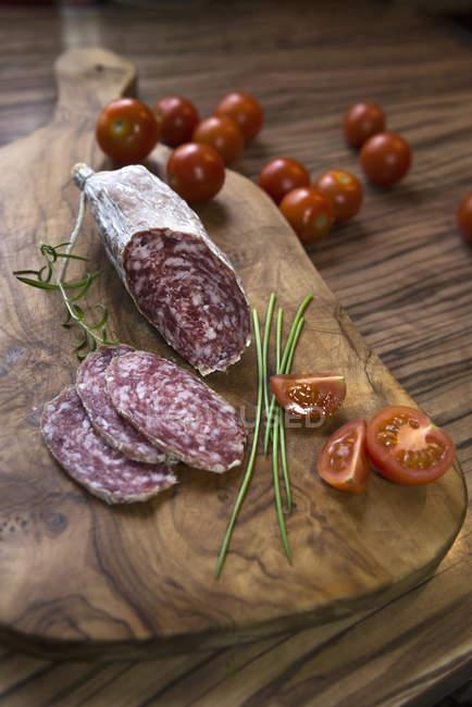 Palo de salchicha con tomate sobre una tabla para picar - foto de stock