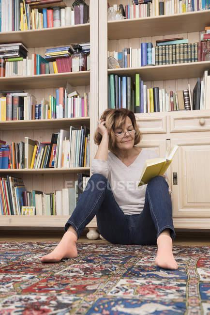 Frau sitzt am Boden im Bücherregal und liest — Stockfoto